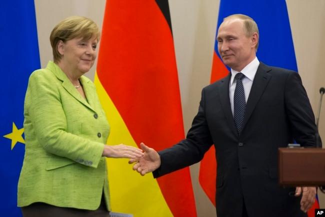 Russian President, Vladimir Putin and German Chancellor Angela Merkel shake hands after their talks in Putin's residence in the Russian Black Sea resort of Sochi, Russia, May 2, 2017.