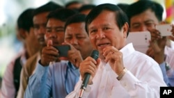Cambodian Vice President of the National Assembly Kem Sokha, also vice president of Cambodia National Rescue Party, foreground, delivers a speech during a Buddhist ceremony to mark 18th anniversary in Phnom Penh, Cambodia, Monday, March 30, 2015.