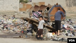 Neighbors collect trash from piles on the street in the hope that government trucks will soon remove the growing stacks of garbage from Mosul, Iraq, Jan. 9, 2017. (H. Murdock/VOA)