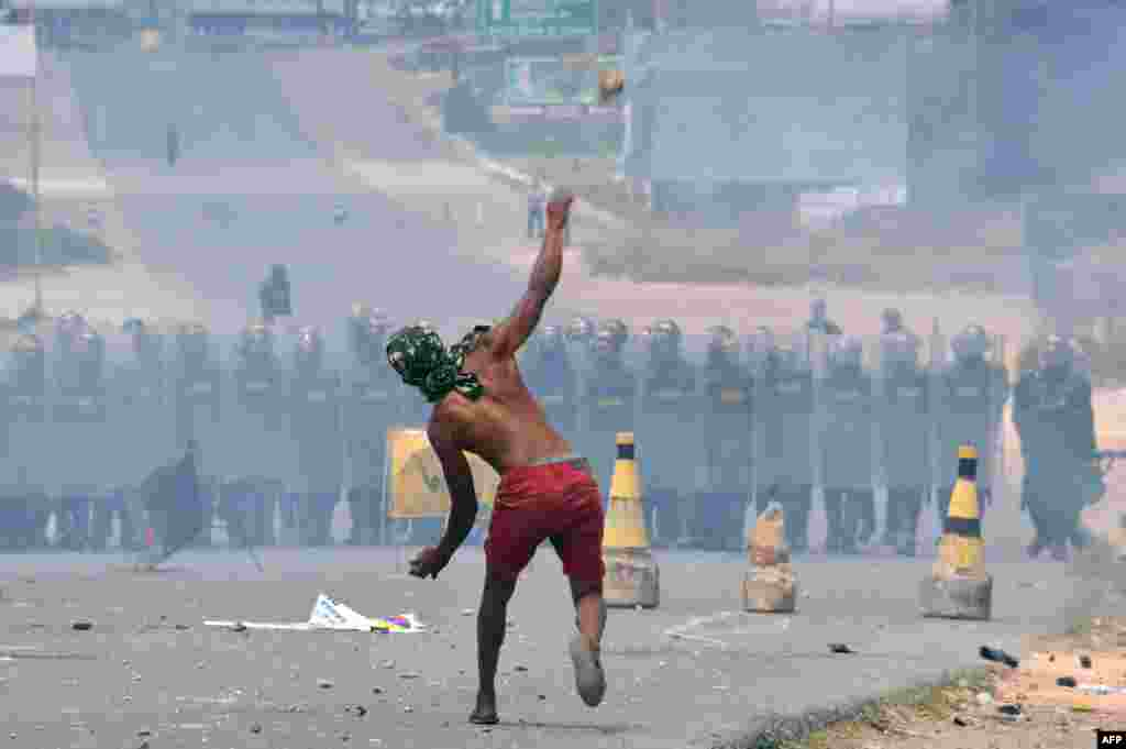 Demonstrators throw stones at Venezuelan Bolivarian National Guard members standing guard in the Venezuela-Brazil border, in Pacaraima, Roraima state, Brazil.