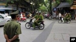 Policemen on motorcycle in Hanoi, Vietnam, June 11, 2010
