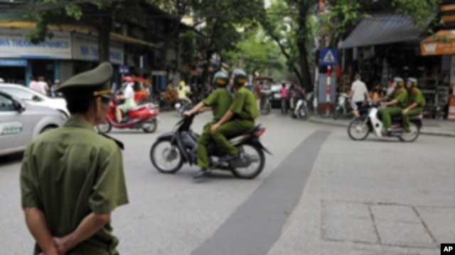 Policemen on motorcycle in Hanoi, Vietnam, June 11, 2010