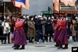 Warga mengenakan masker saat menyaksikan upacara peragaan pergantian Pengawal Kerajaan, di depan gerbang utama Istana Deoksu di Seoul, Korea Selatan, Jumat, 13 November 2020.