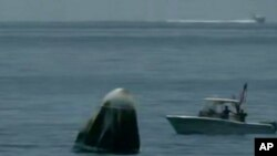 Una captura de video de NASA TV, muestra la cápsula de SpaceX flotando en el Golfo de México el domingo 2 de agosto de 2020.