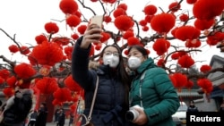 Visitors wearing face masks against pollution take pictures of themselves at the temple fair at Ditan Park (the Temple of Earth) as the Lunar New Year of the rooster is celebrated, in Beijing, China, Jan. 28, 2017.