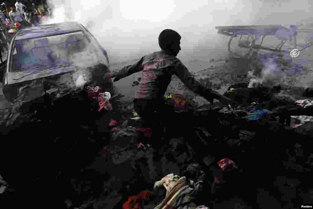 A boy tries to control a fire after vehicles were torched and vandalized by Jamaat-e-Islami party activists during clashes with police in Dhaka, Dec. 13, 2013.