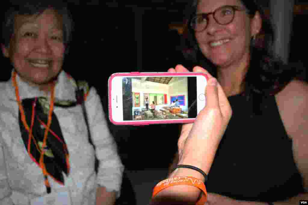 A guest shows photos of a partnering​ school of Caring for Cambodia at a Washington, DC fundraiser and silent auction organized by the non-profit to help support 21 impoverished schools in Cambodia's Siem Reap province, May 4, 2017. (VOA Khmer)