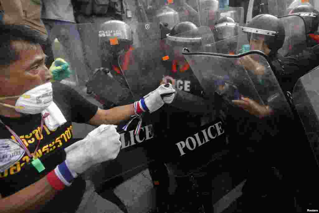 An anti-government protester fights with police at a barricade near Government House in Bangkok, Nov. 25, 2013.