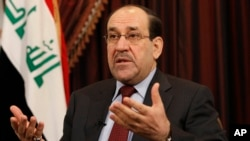 FILE - In this Dec. 3, 2011, file photo, Iraq's Shiite Prime Minister Nouri al-Maliki talks during an interview with The Associated Press in Baghdad, Iraq