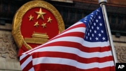 FILE - An American flag is flown next to the Chinese national emblem during a welcome ceremony for visiting U.S. President Donald Trump outside the Great Hall of the People in Beijing, Nov. 9, 2017. China has criticized a U.S. government report that portrays Beijing as a potential nuclear adversary and called on Washington to honor its commitments to reduce its own arsenal.