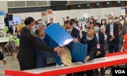 香港选管会主席冯骅(前排右二)与政制及内地事务局局长曾国卫(左二)9月19日晚在会展点票中心,监督选委会选举首个投票箱的开票过程 (美国之音/汤惠芸)