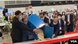 香港選管會主席馮驊(前排右二)與政制及內地事務局局長曾國衛(左二)9月19日晚在會展點票中心,監督選委會選舉首個投票箱的開票過程 (美國之音湯惠芸)