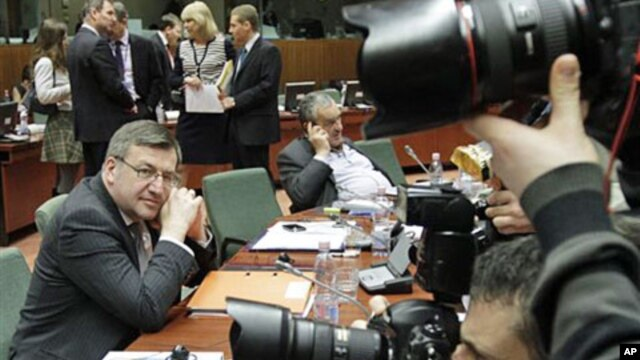 Belgium's FM Steven Vanackere (L) watches the media during an EU foreign ministers meeting at the European Council building in Brussels, Feb 21 2011
