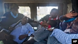FILE - Protesters are beaten with wooden clubs inside the back of a police pickup truck after being arrested outside the Parliament building in Nairobi, Kenya, in December 2014.