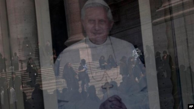 Tourists are reflected in a portrait of Pope Benedict XVI's in St. Peter's Square, a day before the Pope's last general audience, the Vatican, Feb. 26, 2013.