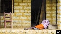 Seorang penderita ebola berbaring di lantai di luar rumahnya di pinggiran ibukota Freetown, Sierra Leone (21/10). Ebola telah menewaskan 4.900 orang lebih.