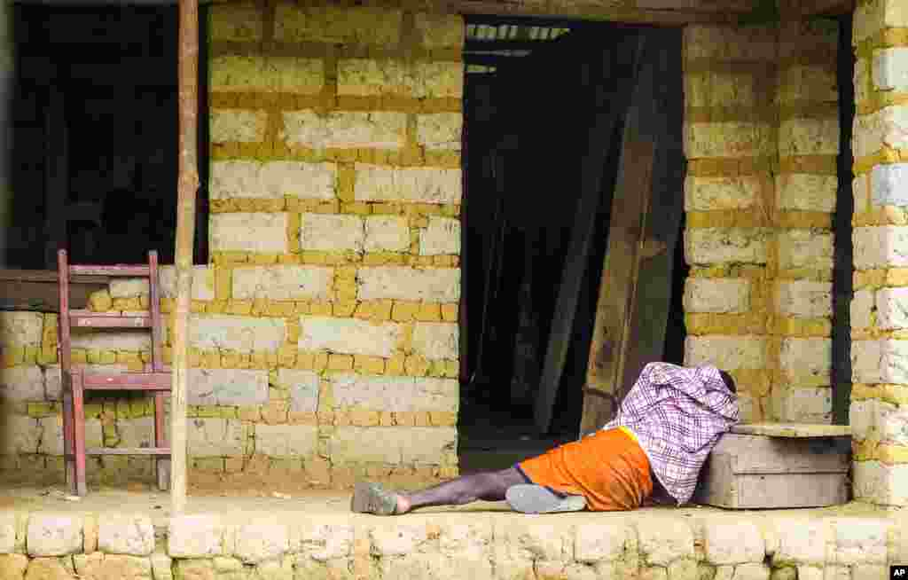 A man suffering from the Ebola virus lies on the floor outside a house in Port Loko Community, on the outskirts of Freetown, Sierra Leone.