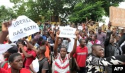 """FILE - People hold placards reading """"Free Ras Bath"""", a young radio presenter Mohamed Youssouf Bathily also known as """"Rasbath"""" who had been arrested, as they take part in a demonstration in front of Bamako's court, Aug. 17, 2016."""
