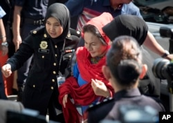 FILE - Rosmah Mansor, center, wife of former Malaysian prime minister Najib Razak, arrives at the country's Anti-Corruption Agency for questioning in Putrajaya, Malaysia, June 5, 2018.