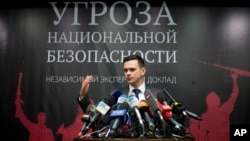"Russian opposition activist Ilya Yashin speaks while presenting a report on Chechen leader Ramzan Kadyrov, in Moscow, Feb. 23, 2016. The banner behind him reads: ""National Security Threat."""