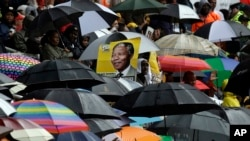 A portrait of Nelson Mandela is seen through a sea of umbrellas during his memorial service at the FNB Stadium in Soweto, near Johannesburg, Dec. 10, 2013.