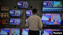 Prodavac gleda obraćanje premijera Narendre Modija nadiciji, preko TV ekrana u prodavnici u Mumbajiju, Indija, 27. marta 2019.