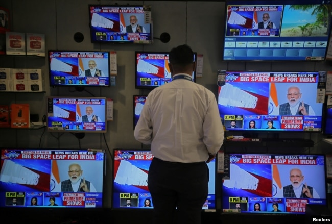 FILE - A salesman watches Prime Minister Narendra Modi addressing to the nation, on TV screens inside a showroom in Mumbai, India, March 27, 2019.
