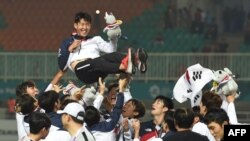 Para pemain sepak bola Korsel mengusung Son Heung-min setelah memenangkan medali emas Asian Games dalam laga final yang digelar Bogor, 1 September 2018. (Foto: AFP)