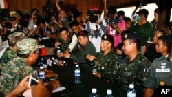 Thai army commander Tarakorn Thammavinthon, seated second right, gestures during a meeting with his Cambodian counterpart at the disputed Cambodia-Thai border in Preah Vihear Province, Cambodia, Tuesday, Nov. 12, 2013.