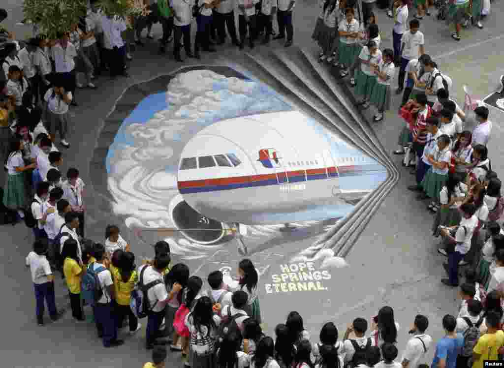 Students gather around a three dimensional artwork, based on the missing Malaysia Airlines flight MH370, that was painted on a school ground in Makati city, metro Manila, Philippines.