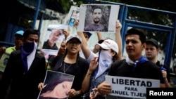 """Des proches et des amis tiennent des photos de leurs proches lors d'une manifestation pour exiger la libération des manifestants détenus lors de manifestations antigouvernementales devant une prison à Managua, au Nicaragua, le 2 juillet 2018. Le panneau indique """"Liberté pour Manuel Tijerino"""". REUTERS / Jorge Cabrera"""