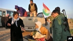 Kurdish soldiers help move an elderly Yazidi woman after Yazidis were released from Islamic militants.