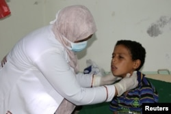 FILE - A pediatrician attends to a boy infected with diphtheria at the al-Sadaqa teaching hospital in the southern port city of Aden, Yemen, Dec. 18, 2017.