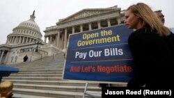 Una funcionaria del Senado coloca uno de los posters diseñados para un evento donde participó el líder de la mayoría demócrata en el Senado, Harry Reid, promoviendo el incremento del techo de la deuda.