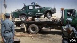 Sebuah mobil polisi yang rusak akibat serangan bom bunuh diri di Lashkar Gah, Propinsi Helmad, Afghanistan (27/9).