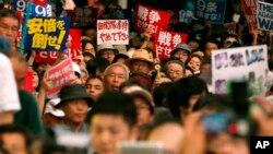 15일 일본 도쿄에서 집단자위권에 반대하는 시위대가 '전쟁 반대', '아베 반대' 등 푯말을 들고 거리행진을 하고 있다.