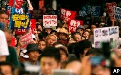 日本国会通过扩充军事力量的防卫法案后,抗议者在国会大厦前举行反战示威集会。