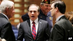 FILE - In this Dec. 14, 2015, file photo, U.S. Department of Veterans Affairs for Health Undersecretary Dr. David Shulkin (c) talks with attendees prior to testifying about the current state of the VA Medical Center in Phoenix at a Senate Veterans' Affairs Committee field hearing in Gilbert, Ariz.