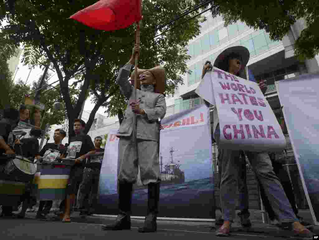 Protesters display placards while shouting slogans outside the Chinese Consulate in Manila against China's construction in a disputed area of the South China Sea, June 12, 2014.