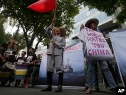 """2014年6月菲律宾人在中国驻马尼拉领事馆外示威,有人手持标语:""""世界恨你,中国"""""""