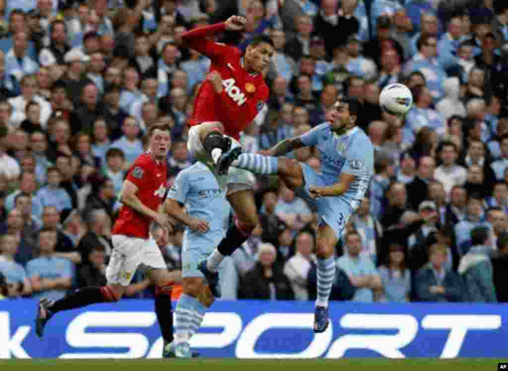 Manchester City's Carlos Tevez, right, competes for the ball with Manchester United's Chris Smalling during the English Premier League soccer match between Manchester City and Manchester United at the Etihad Stadium in Manchester, Monday, April 30, 2012.