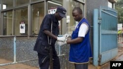A police officer helps a worker to put on his gloves to protect himself from virus infection, July 31, 2012 at the Mulago Hospital in Kampala.