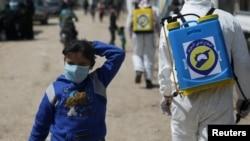 Seorang anak perempuang pengungsi Suriah mengenakan masker wajah, sementara anggota Pertahanan Sipil Suriah menyanitasi kamp Bab Al-Nour untuk mencegah penyebaran virus corona di Azaz, Suriah, 26 March 2020.