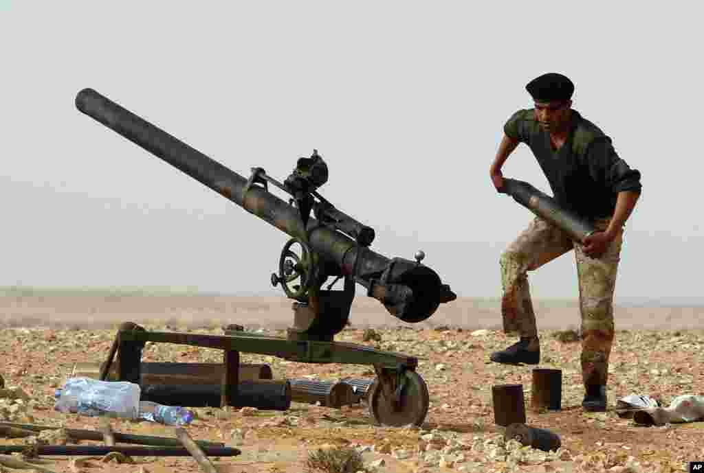 A rebel fighter carries a cannon shell during a battle near Ras Lanuf, Libya, March 04, 2011. (Reuters Image)
