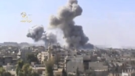 This image taken from video obtained from the Ugarit news network, which has been authenticated based on its contents and other AP reporting, shows smoke rising from the city following heavy bombing from military warplanes, in Deir el-Zour's Jbeileh neigh
