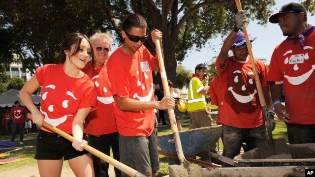 Mexican actress/singer Dulce Maria, far left, helps to build a children's playground at City of Lynwood Park, Aug. 29, 2012, in Lynwood, California.