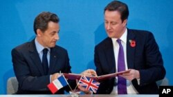 French President Nicolas Sarkozy (L), and British Prime Minister David Cameron exchange copies after signing a treaty during an Anglo-French summit at Lancaster House in central London, 2 Nov 2010