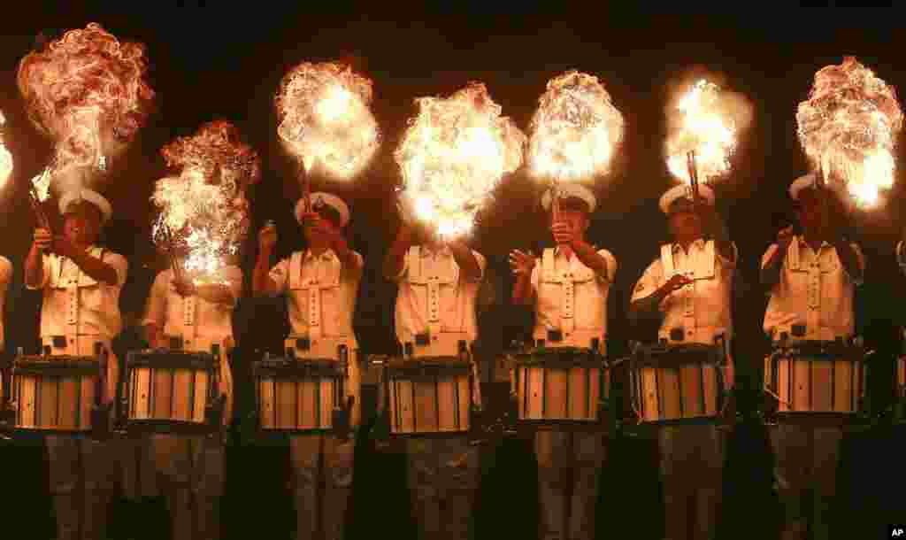 Members of the Indian Navy band perform a fire act during rehearsals for Naval Day celebrations in Mumbai.