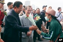 Cambodia's Prime Minister Hun Sen, left, gives a bouquet of flowers to a passenger who disembarked from the MS Westerdam, owned by Holland America Line, at the port of Sihanoukville, Cambodia, Friday, Feb. 14, 2020.