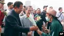 PM Kamboja Hun Sen (kiri) memberikan karangan bunga untuk seorang penumpang kapal pesiar MS Westerdam yang diperkenankan mendarat di pelabuhan Sihanoukville, Kamboja, Jumat, 14 Februari 2020.
